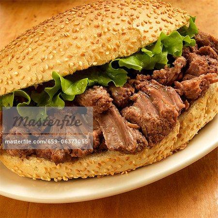 Pot Roast Sandwich with Lettuce on a Sesame Seed Bun