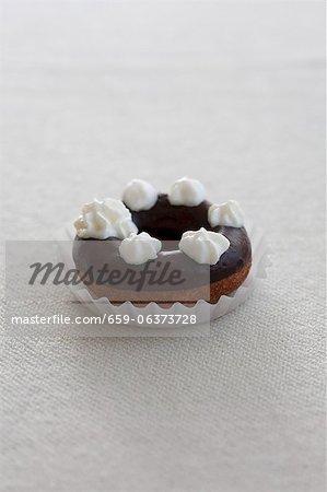 A doughnut with chocolate glaze and blobs of cream