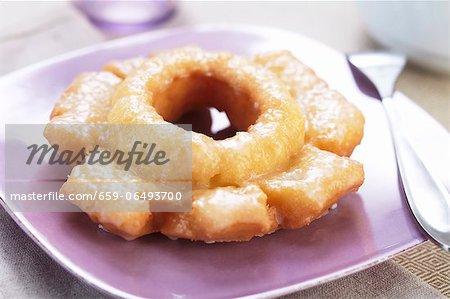 A Glazed Doughnut on a Purple Plate