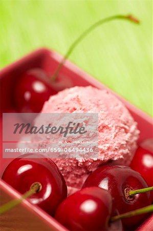 A scoop of cherry ice cream with fresh cherries