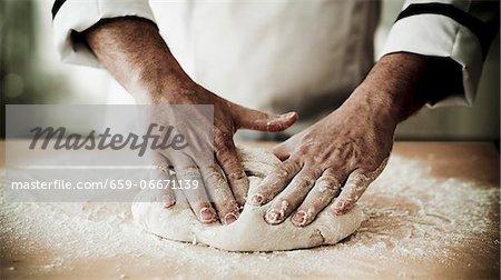 A chef kneading pizza dough