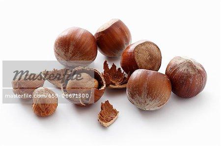 A number of whole hazelnuts and hazelnut shells
