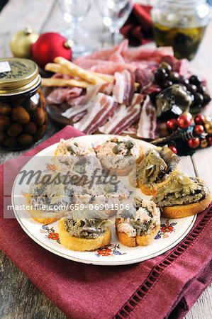Mixed bruschetta topped with tuna and caper paste and artichoke paste