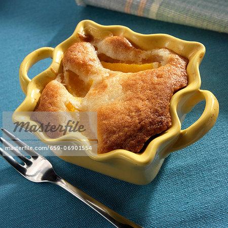 Individual Peach Cobbler in a Yellow Baking Dish