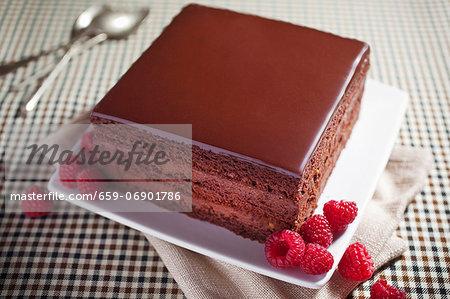 A slice of chocolate cake with fresh raspberries