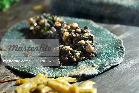 A quesadilla made with a blue corn tortilla with huitlacoche (corn fungus, Mexico)
