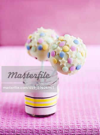Cake pops with white chocolate glaze, mini stars and sugar decorations