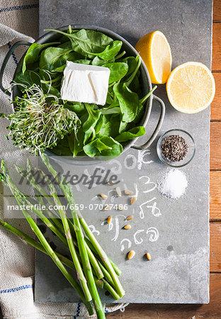 A still life of spinach, asparagus, cress, feta, pine nuts, lemons, salt and pepper