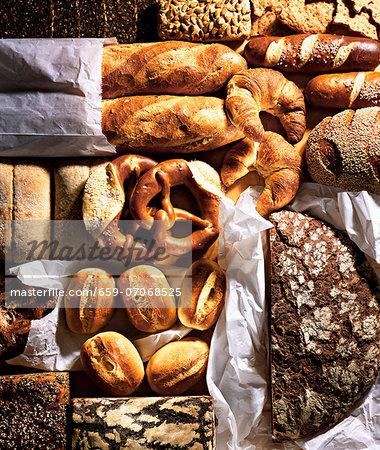 Assorted breads, rolls, pretzels and croissants on baking parchment