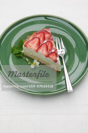 A slice of quark cake with fresh strawberries