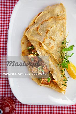 Pancake filled with fried cod, avocado and fresh oregano