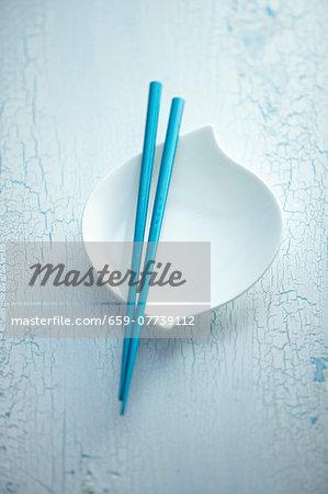 Blue chopsticks balanced over a white bowl