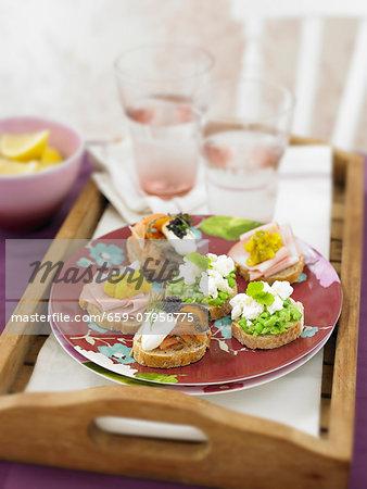 Mini sandwiches with ham, salmon and pea spread
