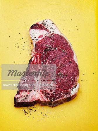 A raw T-bone steak seasoned with salt and pepper