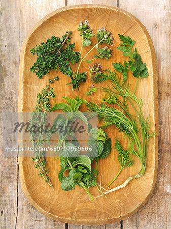 Fresh herbs on a wooden platter: thyme, lemon thyme, oregano, parsley, mint, dill