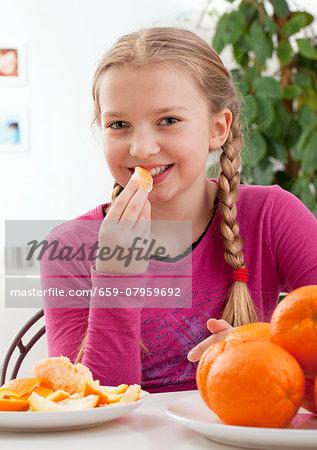 A girl eating an orange