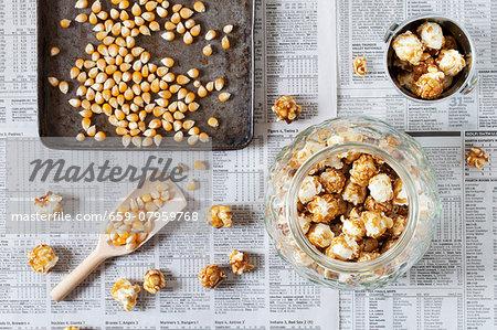A jar of caramel popcorn next to kernels on a baking tray