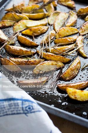 Roasted potato wedges on a baking tray (close-up)
