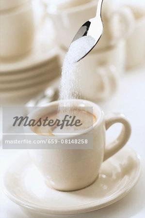 Sugar being added to an espresso