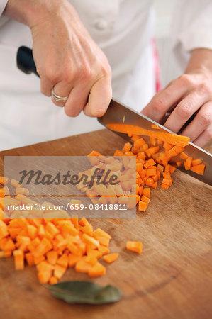 A chef dicing carrots
