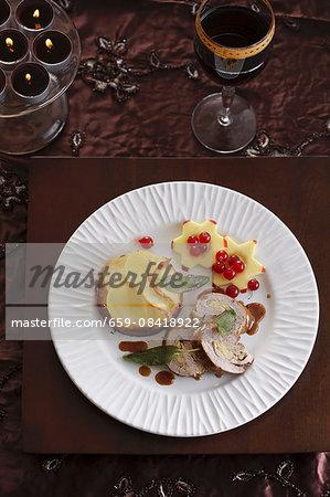 Roast pork roulade with potato gratin, apple stars and redcurrants