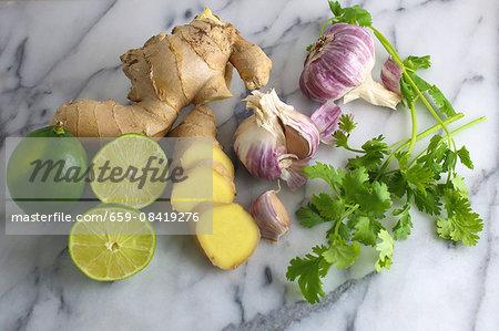 an arrangement of limes, ginger, garlic and coriander