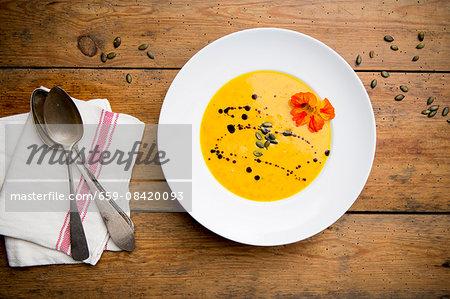 Cream of pumpkin soup with pumpkin seeds, pumpkin seed oil and nasturtium flowers