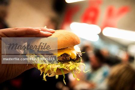 A person holding a hamburger