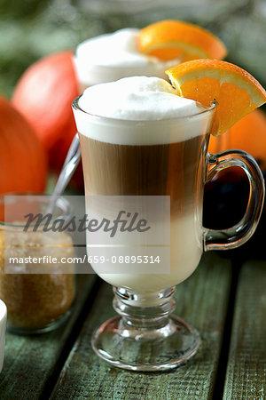 A latte macchiato garnished with a slice of orange