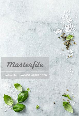 Basil leaves, sea salt and green peppercorns on a marble platter
