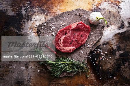 A beef steak, salt, garlic, a chilli pepper and herbs