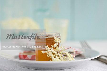 Elderberry jam in a jar decorated with elderflowers