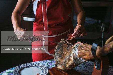 Unrecognizable woman slicing Serrano ham