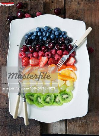 Fruit salad arranged in rainbow stripes on a serving platter