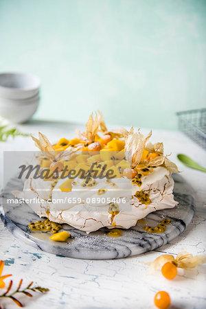 Pavlova with cream, mango, passion fruit and physalis