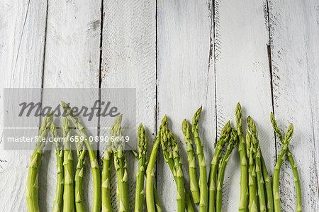 Green asparagus on white wood