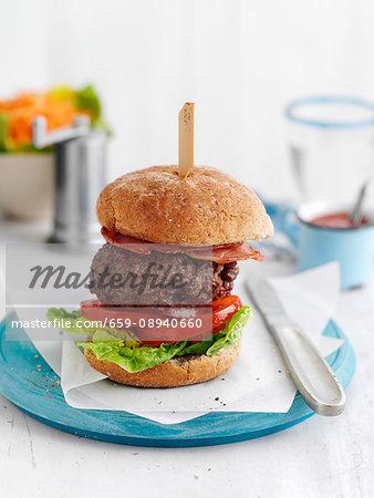 A BLT burger on a blue plate