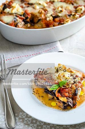Parmigiana di melanzane with tomatoes, mozzarella, oregano, olive oil, basil and ricotta
