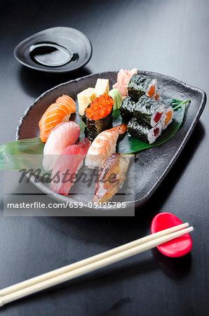 Japanese fresh mixed sushi platter with salmon, tuna, yellowtail, shrimp nigiri, salmon maki, tuna maki on a black plate and black table