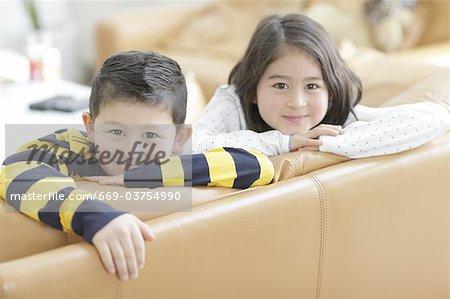 Children leaning against sofa