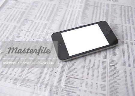 Blank smartphone and newspaper
