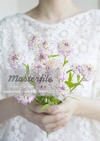 Hands holding a flower bouquet