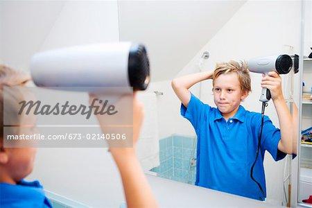 Boy blow-drying hair in bathroom mirror