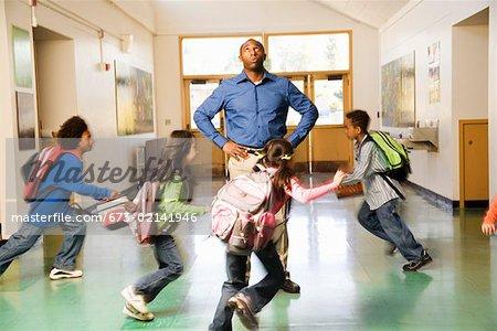 Blurred motion shot of students running past teacher