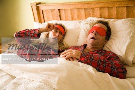 Woman peeking at man wearing eye mask
