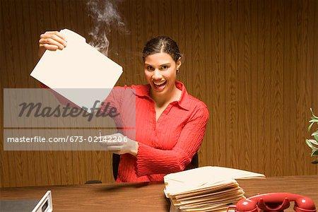 Businesswoman burning files at desk