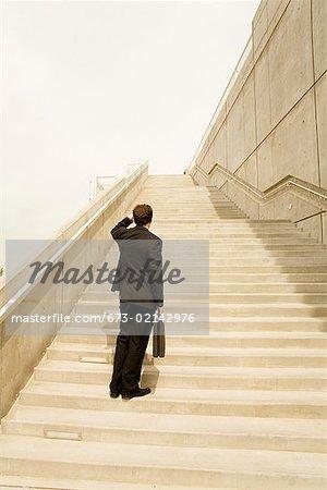 Businessman looking up steps