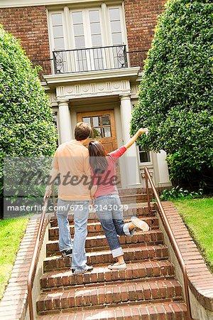 Hispanic couple walking towards house