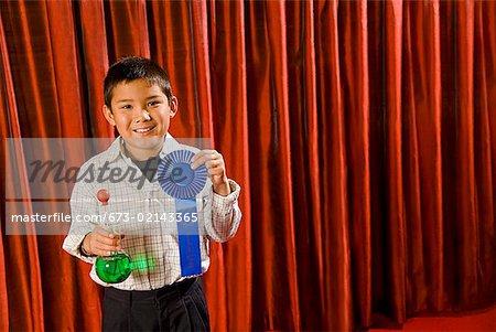Asian boy holding prize ribbon on stage