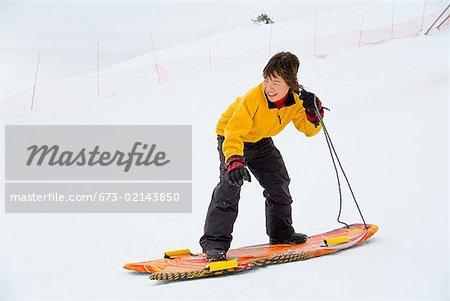 Asian girl riding on sled